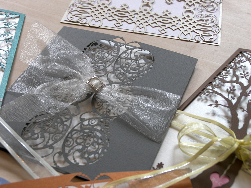 Varying styles and colours of laser cut wedding invitations